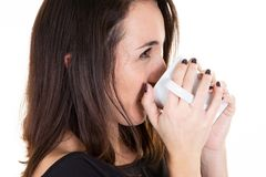 Happy young woman with cup of coffee or cocoa drink at home white wall background stock images