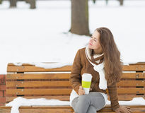 Happy young woman with cup of hot beverage enjoying winter Royalty Free Stock Photo