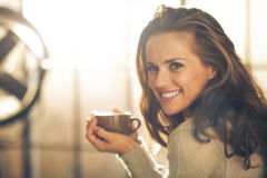 Happy young woman with cup of hot beverage Royalty Free Stock Image