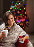 Happy young woman with cup of hot chocolate watching tv stock photos