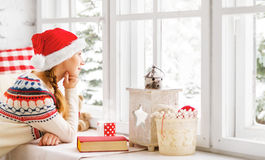 Happy young woman with cup of hot tea and book in winter window Royalty Free Stock Images