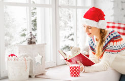 Happy young woman with cup of hot tea and book in winter window Royalty Free Stock Image