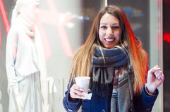 Happy young woman with a cup of hot tea in winter walk outdoors. Female hand holding hot cup of coffee in winter. girl drinking hot coffee Stock Images