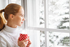 Happy young woman with cup of hot tea in winter window Christmas royalty free stock photos