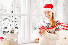 Happy young woman with cup of hot tea in winter window Christmas Stock Image