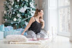 Happy young woman with looking to the winter window Christmas morning. Happy young woman with cup of hot tea in winter window Christmas morning. the girl is Stock Images