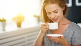 Happy young woman with cup of morning coffee in bed Royalty Free Stock Image