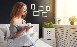 Happy young woman with cup of morning coffee in bed Stock Photography