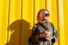 Happy young woman with curly red hair drinking coffee against yellow wall. Modern summer girl chilling out. Happy young woman with curly red hair drinking coffee Stock Photo