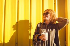Happy young woman with curly red hair drinking coffee against yellow wall. Modern summer girl relaxing and laughing. Outdoors Stock Photos