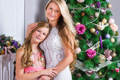Happy young woman with cute teen daughter near the Christmas tre Stock Images
