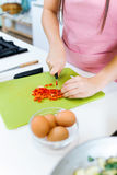 Happy young woman cutting fresh vegetables in kitchen Royalty Free Stock Images