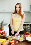 Happy young woman cutting fruits for salad Stock Image