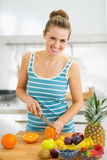 Happy young woman cutting orange in modern kitchen Stock Photos