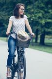 Happy young woman cycling through the park Stock Photos
