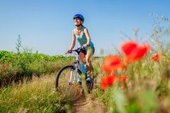 Happy young woman cyclist riding a mountain bicycle in summer field. Girl having fun lifting legs. Happy young woman cyclist riding a mountain bicycle in in stock images