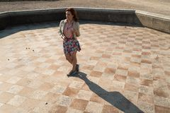 Happy young woman dancing in an empty fountain wearing a colorful skirt royalty free stock image