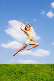 Happy young woman is dancing in a field. Against the backdrop of blue sky Royalty Free Stock Image