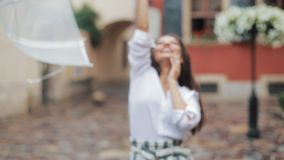 Happy young woman dancing and having fun with umbrella on the street of the old city. Beautiful firl looking and posing stock video footage