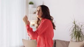 Happy young woman dancing at home. People and leisure concept - happy young woman dancing at home stock video footage