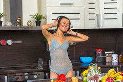 Happy young woman dancing in kitchen with headphones. Royalty Free Stock Photos