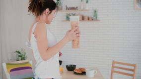 Happy young woman dancing in kitchen wearing pajamas in morning. Girl listens music on smartphone, prepares breakfast. Stock Photography