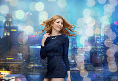 Happy young woman dancing at night club disco. Party, holidays, nightlife and people concept - happy young redhead woman dancing at night club disco over city Stock Photo