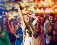 Happy young woman dancing at night club. People, holidays and nightlife concept - happy young women or teen girl in fancy dress with sequins and long wavy hair Stock Image