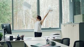 Happy young woman is dancing in office taking off jacket and throwing papers tossing her hair enjoying freedom and good.  stock footage