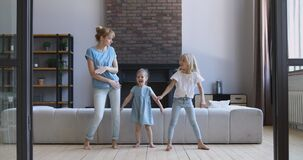 Happy young woman dancing with overjoyed daughters in living room.