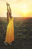 Happy young woman dancing and praising nature. Happy young woman dancing and praising nature with raised hands, enjoying sunset autumn field, gazing into Royalty Free Stock Photo