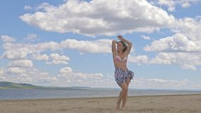 Happy young woman dancing at the tropical beach in blue sea water. The girl is dressed in a silk boho and a swimsuit. She dances to music from the smartphone stock video footage