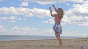 Happy young woman dancing at the tropical beach in blue sea water. The girl is dressed in a silk boho and a swimsuit. She dances to music from the smartphone stock footage