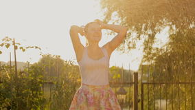 Happy young woman dancing under water from garden sprinkler at sunset stock video