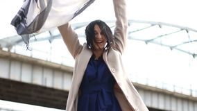 Happy young woman is dancing and is waving her scarf near bridge. stock video