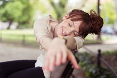 Happy young woman daydreaming on a park bench Royalty Free Stock Photo