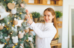 Happy young woman decorate at Christmas tree Royalty Free Stock Photos