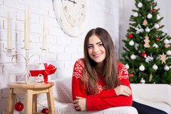 Happy young woman in decorated living room with Christmas tree Stock Photography