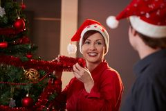 Happy young woman decorating christmas tree Royalty Free Stock Image