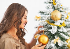 Happy young woman decorating christmas tree with christmas ball Stock Photography