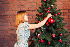 Happy young woman decorating Christmas tree Stock Image