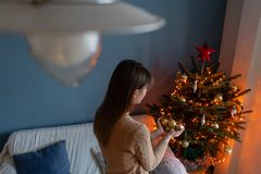 Happy young woman decorating christmas tree at home. Winter holidays in a house interior. Golden and white Christmas. Toys, lights garlands. Natural Danish stock photography