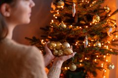 Happy young woman decorating christmas tree at home. Winter holidays in a house interior. Golden and white Christmas. Toys, lights garlands. Natural Danish stock image