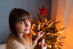 Happy young woman decorating christmas tree at home. Winter holidays in a house interior. Golden and white Christmas. Toys, lights garlands. Natural Danish stock images