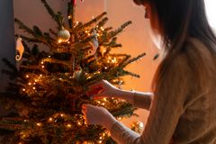 Happy young woman decorating christmas tree at home. Winter holidays in a house interior. Golden and white Christmas. Toys, lights garlands. Natural Danish stock photos