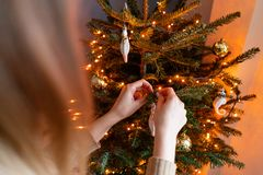 Happy young woman decorating christmas tree at home. Winter holidays in a house interior. Golden and white Christmas. Toys, lights garlands. Natural Danish royalty free stock image