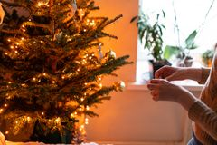 Happy young woman decorating christmas tree at home. Winter holidays in a house interior. Golden and white Christmas. Toys, lights garlands. Natural Danish royalty free stock photography