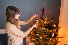 Happy young woman decorating christmas tree at home. Winter holidays in a house interior. Golden and white Christmas. Toys, lights garlands. Natural Danish royalty free stock images