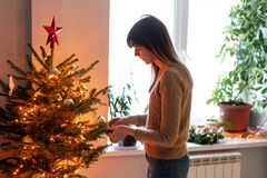 Happy young woman decorating christmas tree at home. Winter holidays in a house interior. Golden and white Christmas. Toys, lights garlands. Natural Danish royalty free stock photos