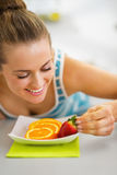 Happy young woman decorating plate with fruits Royalty Free Stock Photo